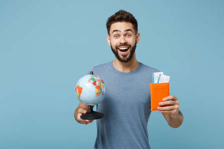 Young excited man in casual clothes posing isolated on blue wall background in studio. People lifestyle concept. Mock up copy space. Holding in hands world globe, passport, boarding pass tickets.