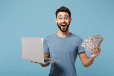Young excited surprised man in casual clothes posing isolated on blue wall background. People lifestyle concept. Mock up copy space. Holding laptop pc computer, fan of cash money in dollar banknotes.