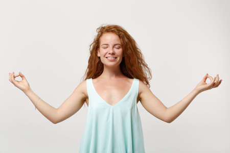 Young smiling redhead woman in casual clothes posing isolated on white background. People lifestyle concept. Mock up copy space. Hold hands in yoga gesture, relaxing meditating, keeping eyes closed.