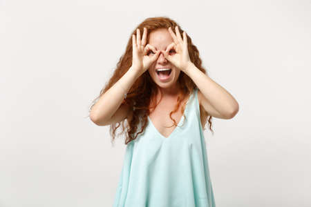 Young cheerful redhead woman in casual light clothes posing isolated on white wall background. People lifestyle concept. Mock up copy space. Holding hands near eyes, imitating glasses or binoculars. Stock Photo