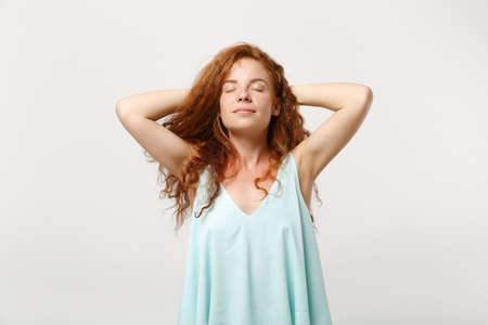 Young relaxed redhead woman in casual light clothes posing isolated on white wall background in studio. People sincere emotions lifestyle concept. Mock up copy space. Sleep with hands behind her head. 免版税图像