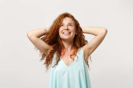 Young smiling pensive redhead woman in casual light clothes posing isolated on white background. People sincere emotions lifestyle concept. Mock up copy space. Looking up with hands behind her head.