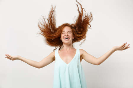 Young laughing redhead woman girl in casual light clothes posing isolated on white background in studio. People lifestyle concept. Mock up copy space. Having fun, fooling around with fluttering hair.
