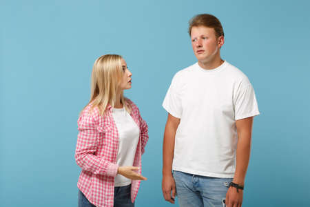 Young fun couple two friends guy girl in white pink empty blank design t-shirts posing isolated on pastel blue background studio portrait. People lifestyle concept. Mock up copy space. Looking upset.