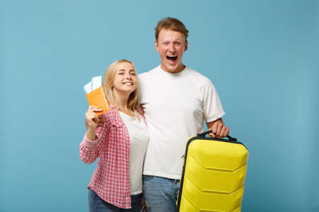 Young cheerful couple two friends guy girl in white pink t-shirts posing isolated on pastel blue background. People lifestyle concept. Mock up copy space. Hold passport boarding pass ticket, suitcase.