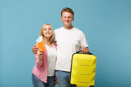 Young smiling couple two friends guy girl in white pink t-shirts posing isolated on pastel blue background. People lifestyle concept. Mock up copy space. Hold passport, boarding pass ticket, suitcase.