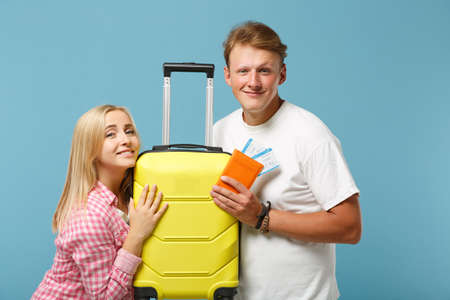 Young smiling couple two friends guy girl in white pink t-shirts posing isolated on pastel blue background. People lifestyle concept. Mock up copy space. Hold passport boarding pass, ticket, suitcase.