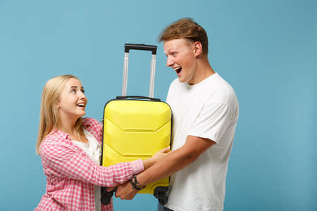 Young joyful couple two friends guy girl in white pink empty blank t-shirts posing isolated on pastel blue background in studio. People lifestyle concept. Mock up copy space. Holding yellow suitcase.