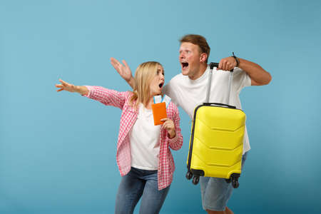 Couple friends guy girl in white pink t-shirts posing isolated on pastel blue background. People lifestyle concept. Mock up copy space. Hold passport boarding pass, ticket, suitcase, running and late.