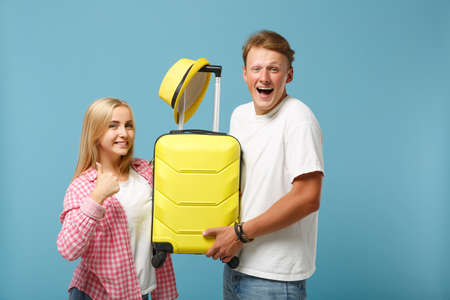 Young funny couple two friends guy girl in white pink t-shirts posing isolated on pastel blue background. People lifestyle concept. Mock up copy space. Hold yellow suitcase and hat showing thumb up.