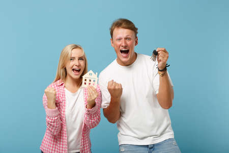 Overjoyed couple two friends guy girl in white pink t-shirts posing isolated on pastel blue background. People lifestyle concept. Mock up copy space. Holding house bunch of keys, doing winner gesture.