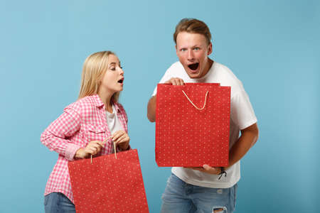Young shocked couple two friends guy girl in white pink t-shirts posing isolated on blue background. Valentines Day, Womens Day, birthday concept. Hold gift certificate, package bag after shopping.