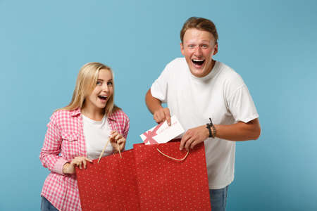 Young funny couple two friends guy girl in white pink t-shirts posing isolated on blue background. Valentines Day, Womens Day, birthday concept. Hold gift certificate, package bag after shopping. Stock Photo