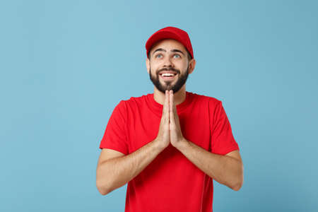 Delivery man in red uniform workwear isolated on blue wall background, studio portrait. Professional male employee in cap t-shirt print working as courier dealer. Service concept. Mock up copy space.