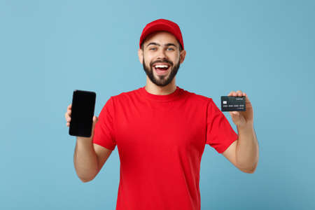 Delivery man in red uniform workwear hold cellphone isolated on blue background, studio portrait. Professional male employee in cap t-shirt working courier dealer. Service concept. Mock up copy space.