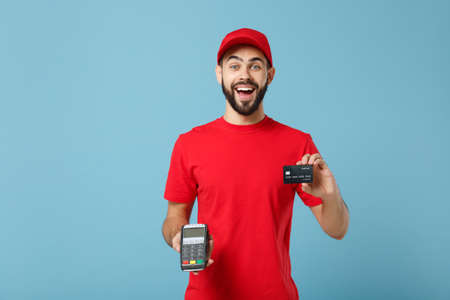 Delivery man in red workwear hold bank payment terminal to process acquire credit card payments isolated on blue background. Employee in cap t-shirt working courier. Service concept Mock up copy space