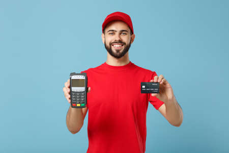 Delivery man in red workwear hold bank payment terminal to process acquire credit card payments isolated on blue background. Employee in cap t-shirt working courier. Service concept Mock up copy space Foto de archivo