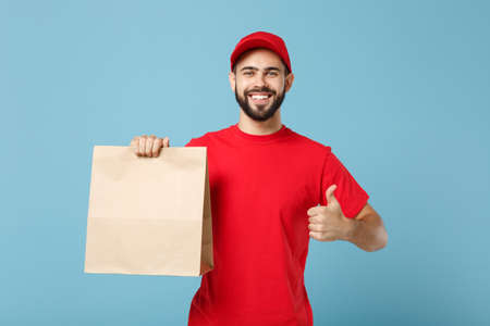 Delivery man in red uniform hold craft paper packet with food isolated on blue background, studio portrait. Male employee in cap t-shirt print working as courier. Service concept. Mock up copy space.