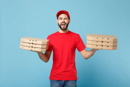Delivery man in red workwear giving food order pizza boxes isolated on blue background, studio portrait. Professional male employee in cap t-shirt print courier. Service concept. Mock up copy space.
