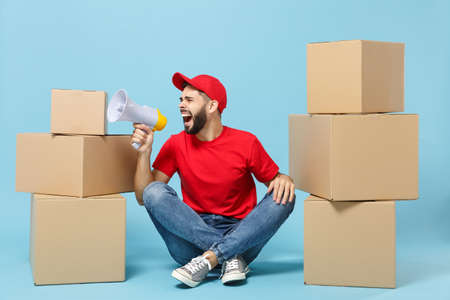 Delivery man in red uniform isolated on blue background, studio portrait. Male employee in cap t-shirt print working as courier dealer sit at empty cardboard box. Service concept. Mock up copy space. Stock Photo