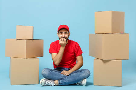 Delivery man in red uniform isolated on blue background, studio portrait. Male employee in cap t-shirt print working as courier dealer sit at empty cardboard box. Service concept. Mock up copy space.