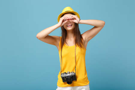 Traveler tourist woman in yellow summer casual clothes, hat with photo camera isolated on blue background. Female passenger traveling abroad to travel on weekends getaway. Air flight journey concept.