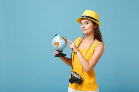 Traveler tourist woman in yellow summer casual clothes, hat with globe, camera isolated on blue background. Female passenger traveling abroad to travel on weekends getaway. Air flight journey concept.