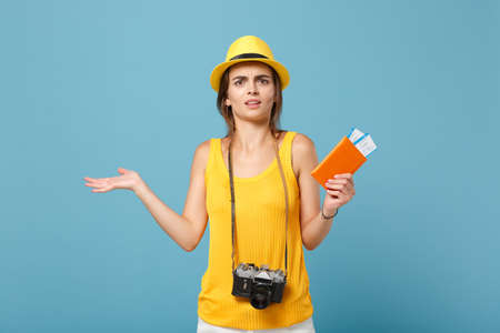 Traveler tourist woman in yellow summer casual clothes hat hold tickets camera isolated on blue background. Female passenger traveling abroad to travel on weekends getaway. Air flight journey concept. Imagens