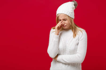 Dissatisfied young woman in white sweater, hat isolated on red background, studio portrait. Healthy fashion lifestyle, people emotions, cold season concept. Mock up copy space. Crying, wiping tears. Stockfoto