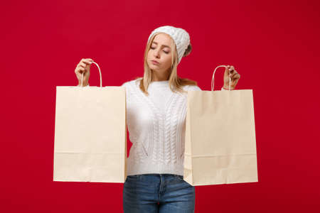 Pretty young woman in white sweater, hat isolated on red wall background in studio. Healthy fashion lifestyle, cold season concept. Mock up copy space. Hold package bag with purchases after shopping. Stock Photo