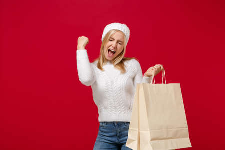 Joyful young woman in sweater, hat isolated on red background. Healthy fashion lifestyle, cold season concept. Mock up copy space. Doing winner gesture, hold package bag with purchases after shopping.
