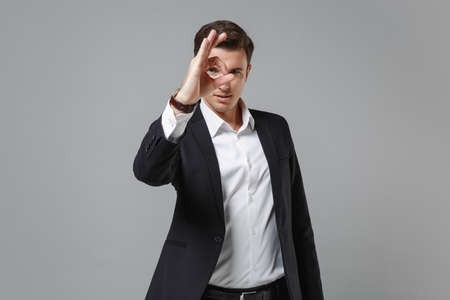 Young business man in classic black suit shirt isolated on grey background. Achievement career wealth business concept. Mock up copy space. Holding hand near eye, imitating eyeglasses or binoculars.