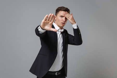 Concerned young business man in classic suit shirt posing isolated on grey background. Achievement career wealth business concept. Mock up copy space. Showing stop gesture with palm, put hand on head.