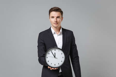 Successful handsome young business man in classic black suit shirt posing isolated on grey wall background studio portrait. Achievement career wealth business concept. Mock up copy space. Hold clock. 版權商用圖片