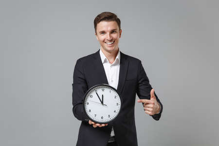 Funny young business man in classic black suit shirt posing isolated on grey background studio portrait. Achievement career wealth business concept. Mock up copy space. Pointing index finger on clock. 版權商用圖片 - 153187825