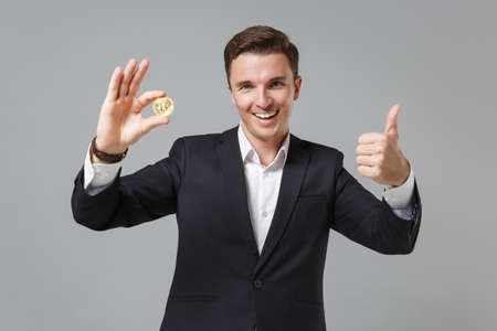 Funny young business man in classic black suit shirt posing isolated on grey background. Achievement career wealth business concept. Mock up copy space. Hold bitcoin future currency, showing thumb up. Zdjęcie Seryjne