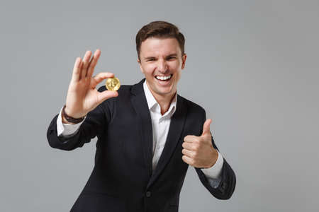 Laughing young business man in classic suit shirt posing isolated on grey background. Achievement career wealth business concept. Mock up copy space. Hold bitcoin future currency, showing thumb up.