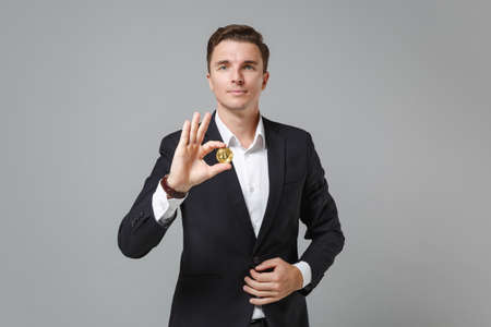 Successful young business man in classic black suit shirt posing isolated on grey background in studio. Achievement career wealth business concept. Mock up copy space. Hold bitcoin, future currency. Zdjęcie Seryjne