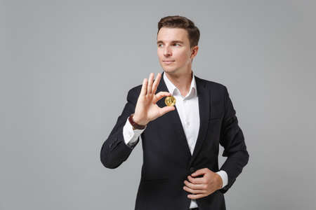 Handsome young business man in classic black suit shirt posing isolated on grey background. Achievement career wealth business concept. Mock up copy space. Hold bitcoin future currency, looking aside. Zdjęcie Seryjne