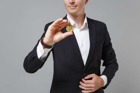 Cropped image of young business man in classic black suit shirt posing isolated on grey wall background. Achievement career wealth business concept. Mock up copy space. Hold bitcoin future currency. Zdjęcie Seryjne
