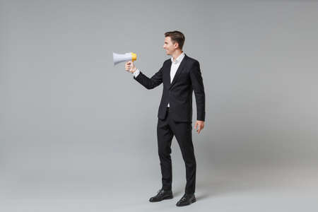 Side view of young business man in classic black suit shirt posing isolated on grey wall background studio portrait. Achievement career wealth business concept. Mock up copy space. Hold megaphone.