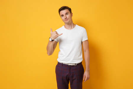 Smiling young man guy 20s in white t-shirt posing isolated on yellow orange wall background. People sincere emotions, lifestyle concept. Mock up copy space. Doing phone gesture like says call me back.