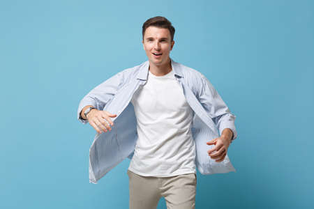Young man guy 20s in casual shirt posing isolated on pastel blue wall background studio portrait. People sincere emotions, lifestyle concept. Mock up copy space. Walking with a fluttering shirt.