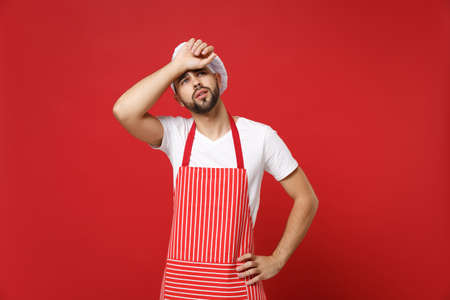 Tired young bearded male chef cook or baker man in striped apron toque chefs hat posing isolated on red background in studio. Cooking food concept. Mock up copy space. Looking up putting hand on head.