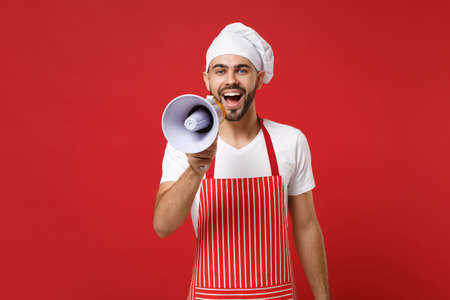 Cheerful young bearded male chef cook or baker man in striped apron white t-shirt toque chefs hat isolated on red background in studio. Cooking food concept. Mock up copy space. Scream in megaphone. Stock Photo