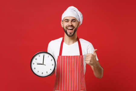 Excited young bearded male chef cook or baker man in striped apron white t-shirt toque chefs hat isolated on red background. Cooking food concept. Mock up copy space. Holding clock, showing thumb up. 版權商用圖片
