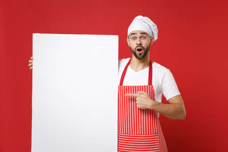 Shocked chef cook or baker man in striped apron white t-shirt toque chefs hat isolated on red background. Cooking food concept. Mock up copy space. Pointing index finger on big empty blank billboard. Stock fotó