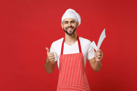 Smiling young male chef cook or baker man in striped apron white t-shirt toque chefs hat isolated on red wall background. Cooking food concept. Mock up copy space. Holding check mark showing thumb up.