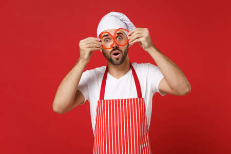 Young male chef cook or baker man in striped apron toque chefs hat isolated on red background. Cooking food concept. Mock up copy space. Hold pepper slices near eyes, imitating glasses or binoculars. Stock Photo