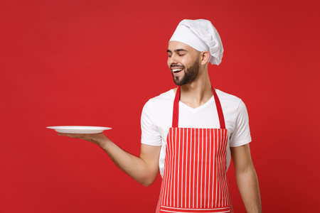 Cheerful young male chef cook or baker man in striped apron toque chefs hat isolated on red background. Cooking food concept. Mock up copy space. Holding empty blank round plate with place for food. Banque d'images